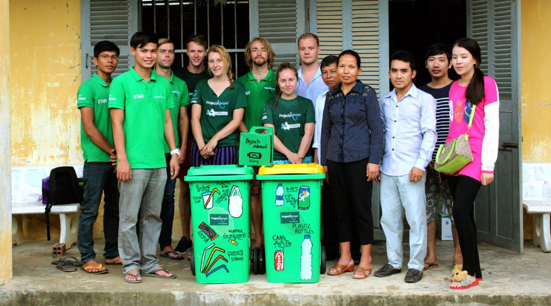 Volunteers and staff pose with the new recycle bins at a local school in Cambodia